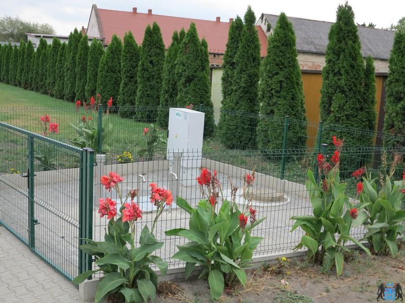 Zdjęcie przepompowni kanalizacji sanitarnej w miejscowości Pągów, urządzenia ogrodzone zielonym płotem, wokół którego rosną czerwone kwiaty.