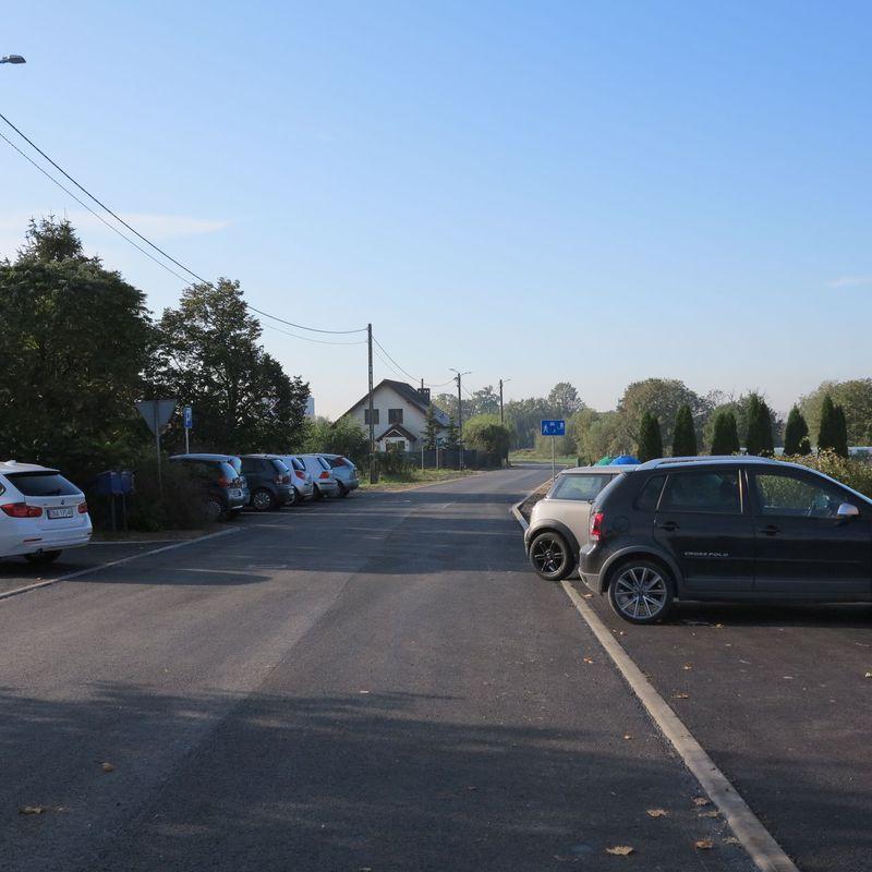 Zdjęcie pokazuje w ujęciu perspektywy nowo wylany asfalt na drodze, z lewej i prawej strony stoją zaparkowane samochody osobowe.