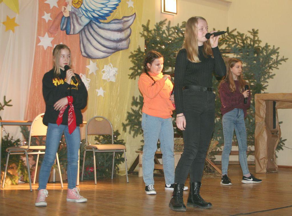 Zdjęcie przedstawia występ czwórki uczniów na scenie podczas wykonywania programu wokalno - tanecznego.