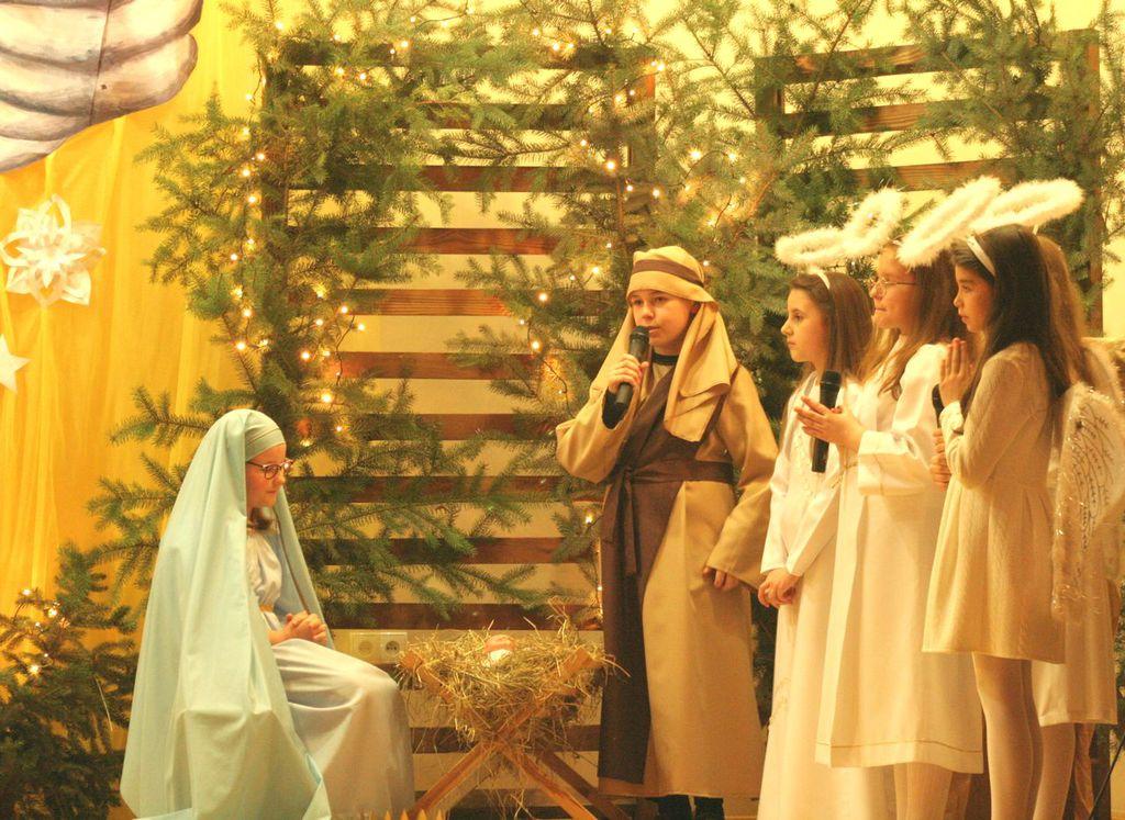 Zdjęcie przedstawia grupę młodzieży  w przebraniach, podczas występów na scenie, grających rolę: Maryi, Józefa oraz aniołów.