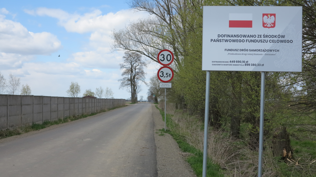 Zdjęcia przedstawia w perspektywie drogę relacji Bukowie – Gorzesław, po lewej stroni e od drogi widać betonowy szary płot, po stronie prawej drogi na pierwszym planie tablica informacyjna z polską flagą i godłem dalej znajdują się znaki drogowe widoczne na tle okolicznych drzew i krzewów.