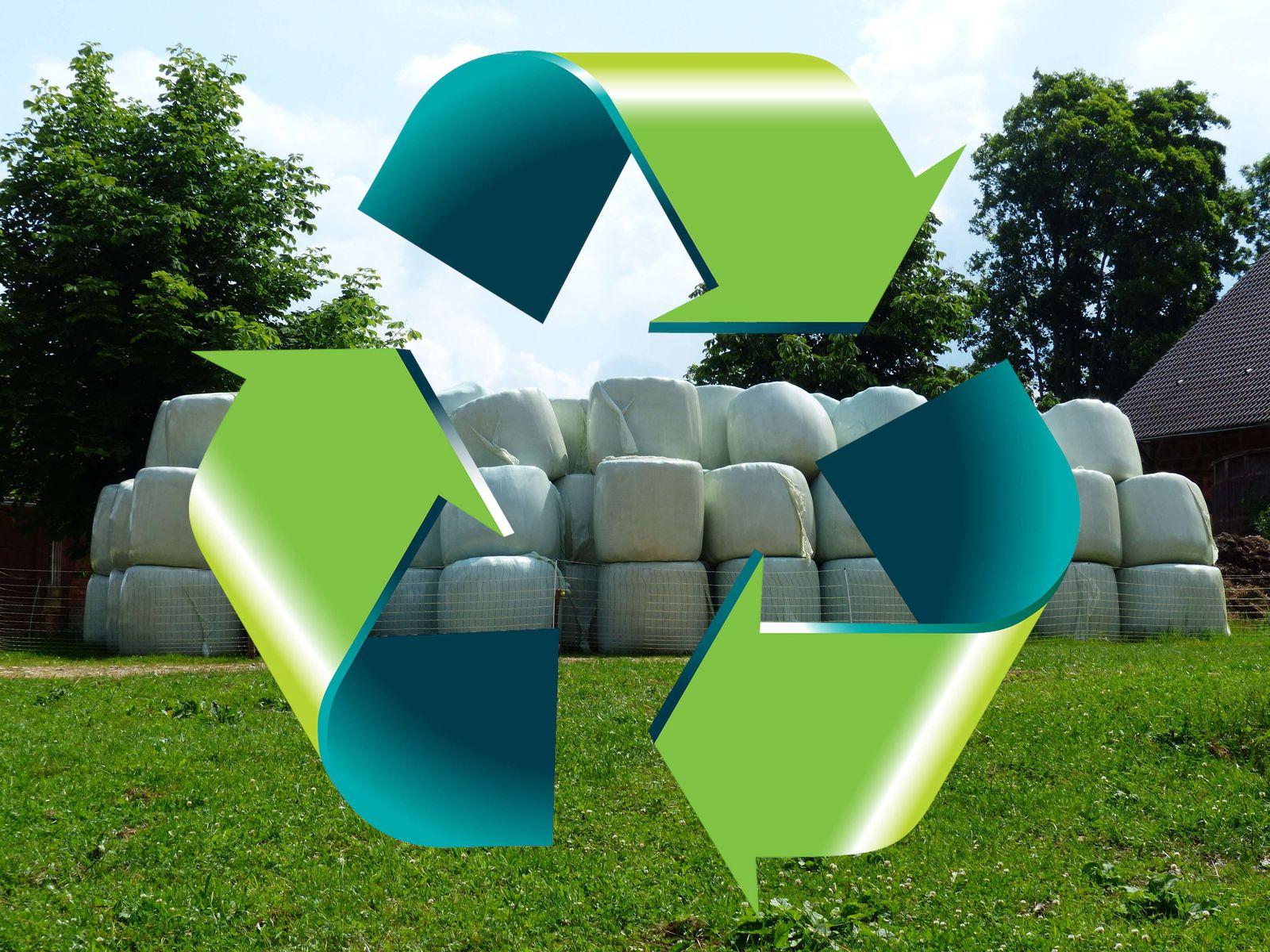 Kompozycja przedstawia symbol recyklingu zawierający trzy zielono-szmaragdowe strzałki, tworzące trójkąt, z grotami skierowanymi zgodnie z ruchem wskazówek zegara, na tle pryzmy białych beli rolniczych położonych na zielonej łące pod drzewami.