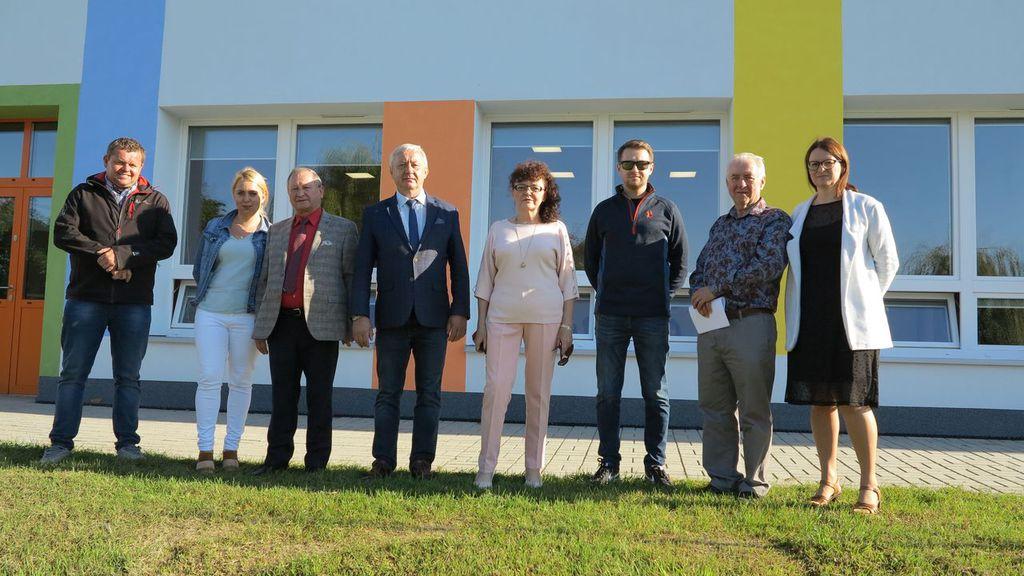 Zdjęcie przedstawia ośmioosobową komisje odbiorową stojącą na trawniku przed budynkiem  Przedszkola w Idzikowicach.