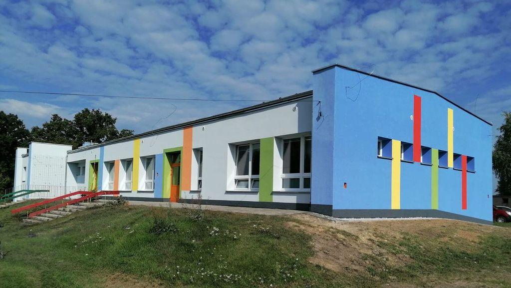 Zdjęcie przedstawia odnowiony budynek Przedszkola w Idzikowicach, którego elewacja została pomalowana na szaro-niebiesko. Pomiędzy oknami kolorowe: czerwone, żółte, pomarańczowe i zielone pasy. Zdjęcie wykonano na tle niebieskiego nieba oraz okalającego budynek trawnika.