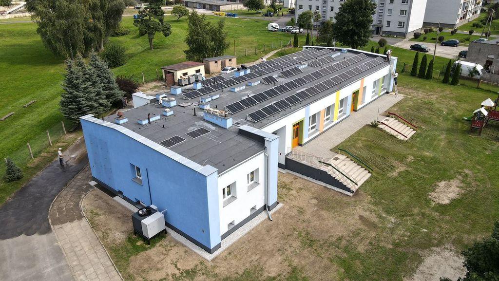 Zdjęcie przedstawia widok budynku Przedszkola w Idzikowicach z góry. Na dachu budynku widać rozmieszczone w rzędach panele fotowoltaiczne.