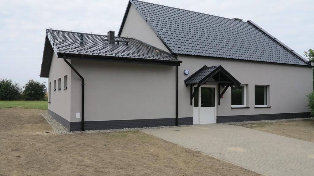 Zdjęcie przedstawia odnowioną świetlicę wiejską w Wojciechowie widok od frontu. Elewacja budynku jest w kolorze szarym, dach wykonano z czarnej  blachodachówki.