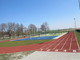 Na pierwszym planie widok bieżni okólnej pięciotorowej w kolorze bordowym, drugi plan przedstawia boisko do gry w piłkę siatkową. Całość na tle drzew i błękitnego nieba.