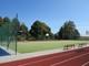 Główna część zdjęcia przedstawia boisko wielofunkcyjne o nawierzchni z trawy syntetycznej, wokół którego stoją ławki.